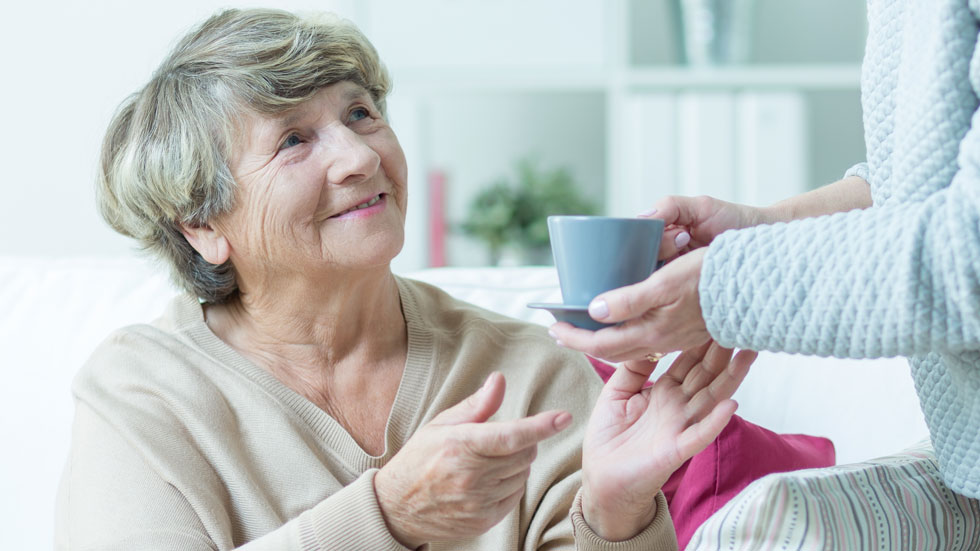 Elderly woman being given cup of tea