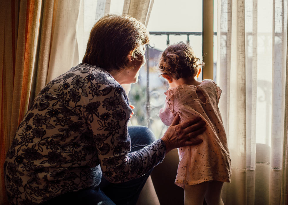 Grandmother with grandchild looking out window
